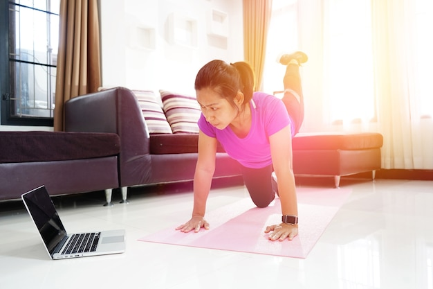 Asian women exercise doing arching back straightening leg up workout at home