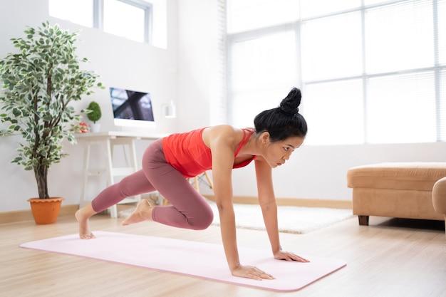 アジアの女性が自宅で屋内で運動する彼女は「山岳賞」を演じる