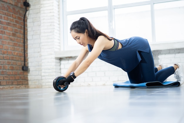 Asian women exercise with roller wheel