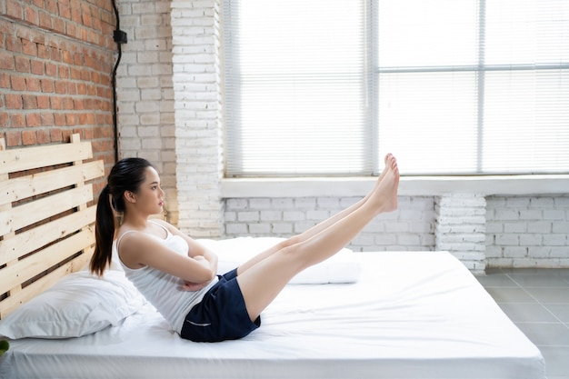 Asian women exercising in bed in the morning, she feels refreshed.
