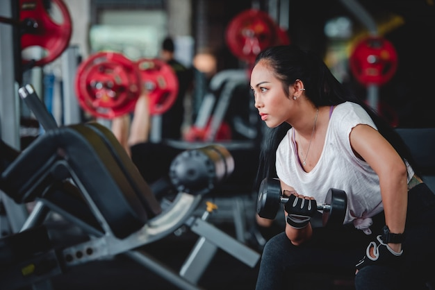 Asian women exercising with dumbbells in the dumbbell bench press are a popular position for young women in fitness.