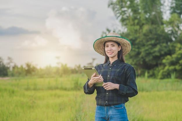 태블릿 개념 스마트 농부를 사용 하여 아시아 여성 농부 프리미엄 사진