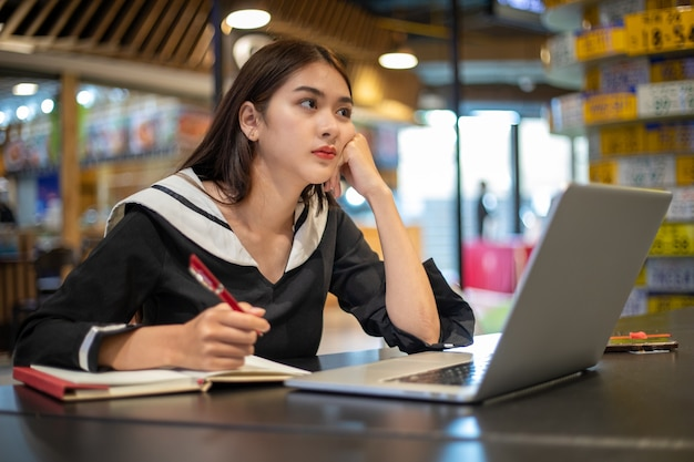 Asian women feel serious about working and studying online with notebook computers.