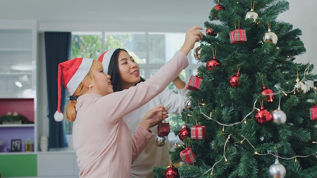 Asian women friends decorate christmas tree at christmas festival. female teen happy smiling celebrate xmas winter holidays together in living room at home.
