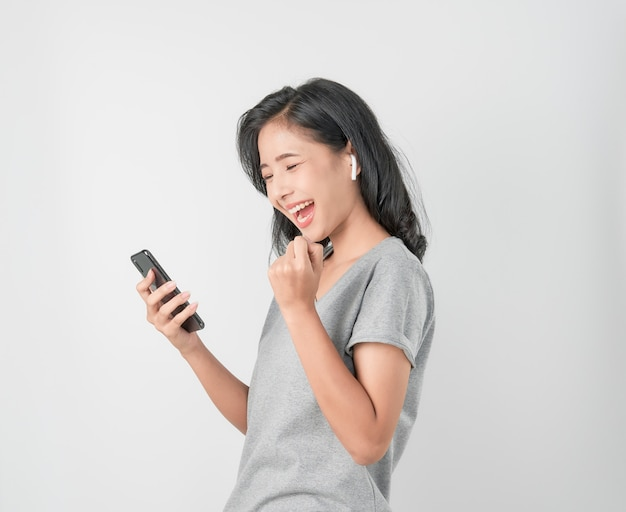 Asian women of happy smiling are listening to music from white headphones. and using hands touch to use various functions, happy mood on blue .
