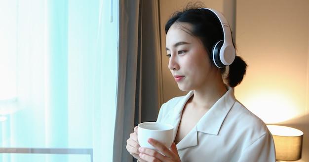 ヘッドフォンを携帯電話で音楽に合わせて、自宅でリラックスした時間にコーヒーを飲んで幸せなアジアの女性