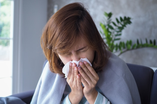 Азиатские женщины имеют насморк и простужаются, кашляют, чихают, лихорадят, болеют на диване в доме.