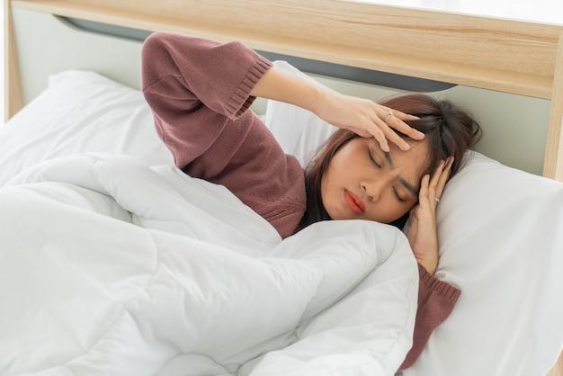 아시아 여성 두통 및 침대에서 자