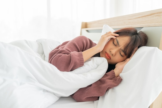 アジアの女性の頭痛とベッドで寝ています。