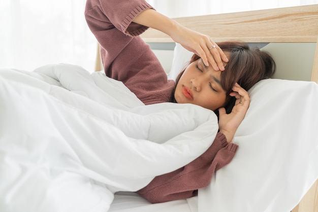 Asian women headache and sleeping on bed