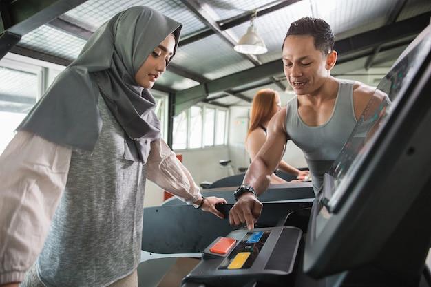 アジアの女性ヒジャーブはトレッドミルで実行されます