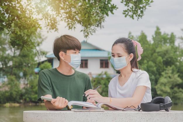 Азиатские женщины, держащие книгу, стоящую на открытом воздухе, снова в школу