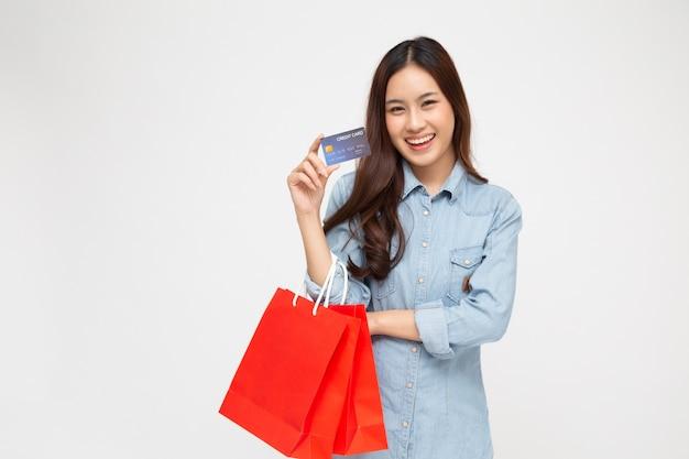 クレジットカードと白で分離された赤いショッピングバッグを保持しているアジアの女性。