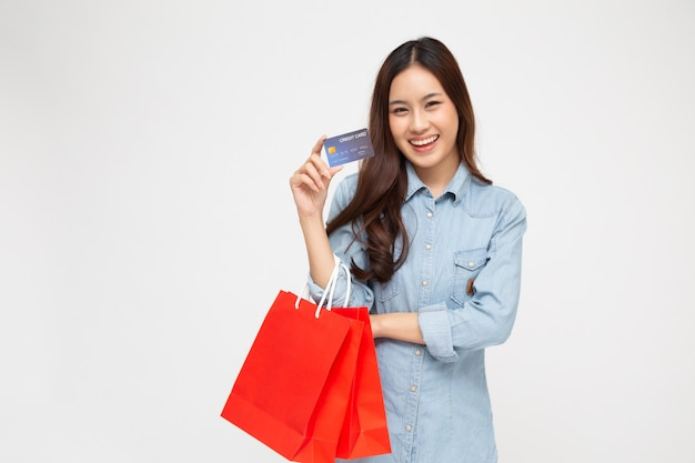 Asian women holding credit card and red shopping bag isolated over white.