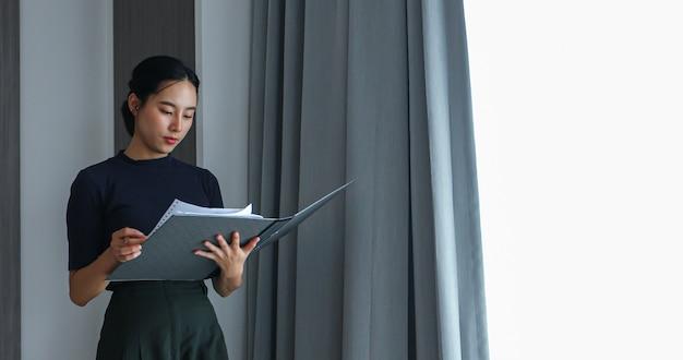 사무실에서 일하기 위해 파일을 들고 문서를 검토하는 아시아 여성
