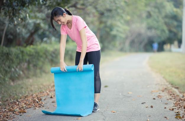 요가 매트를 들고있는 아시아 여성들은 건강을 유지하고 건강을 유지하기 위해 공원에서 요가를 할 것입니다.