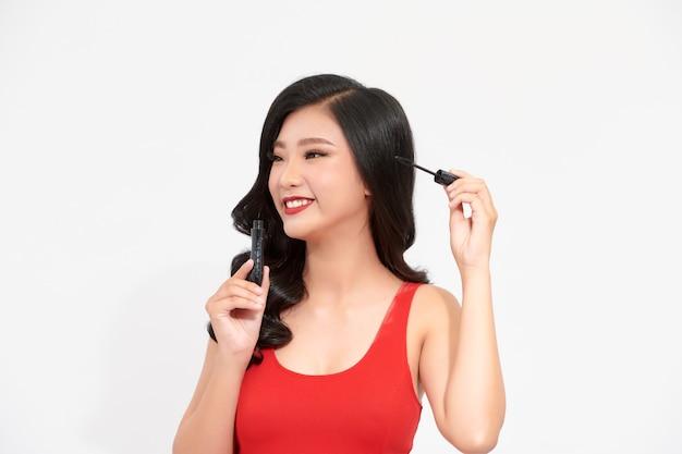 Азиатские женщины в красном платье используют тушь
