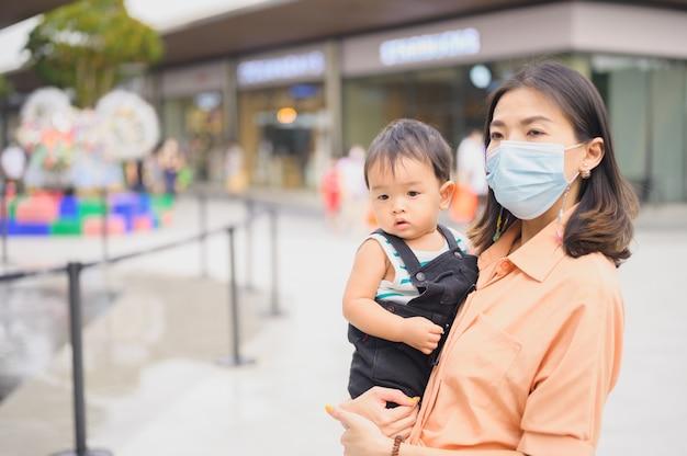 彼女の息子と一緒に保護滅菌医療マスクのアジアの女性。大気汚染、ウイルス、コロナウイルスの概念