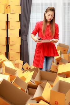 온라인 쇼핑 비즈니스에서 집에서 일하는 빨간 드레스를 입은 아시아 여성