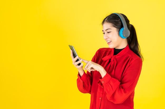 Азиатские женщины в счастливом настроении держат телефон и надевают беспроводные наушники в красное платье.
