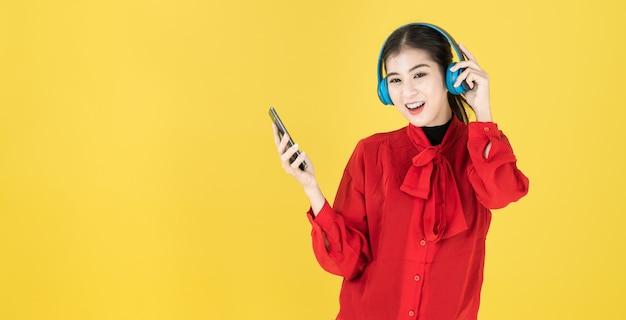 Азиатские женщины в счастливом настроении держат телефон и надевают беспроводные наушники с красным платьем.
