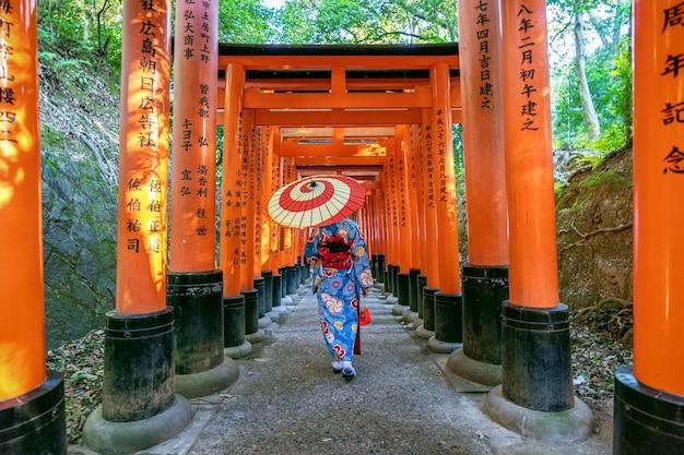 일본 교토의 후 시미이나 리 신사에서 일본 전통 기모노를 입은 아시아 여성.