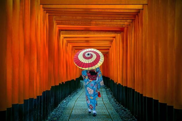 京都の伏見稲荷神社で伝統的な日本の着物を着たアジアの女性。