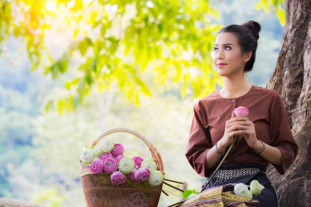 一方で蓮の花を持つヴィンテージのドレスでアジアの女性