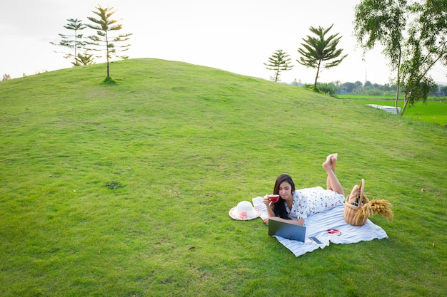 Asian women is lying on the green grass in her garden aerial view