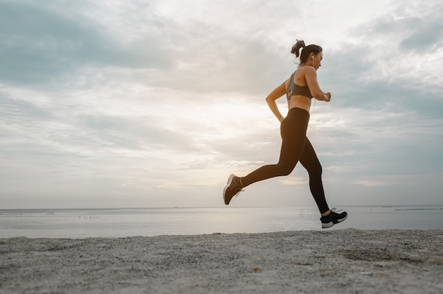 Asian women jogging in the sand on the beach in the morning.exercise,fitness ,workout, gym exercise ,lifestyle and healthy concept.