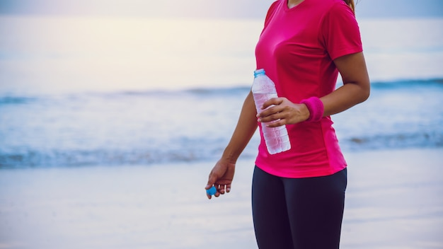 Asian women jogging workout on the beach in the morning.