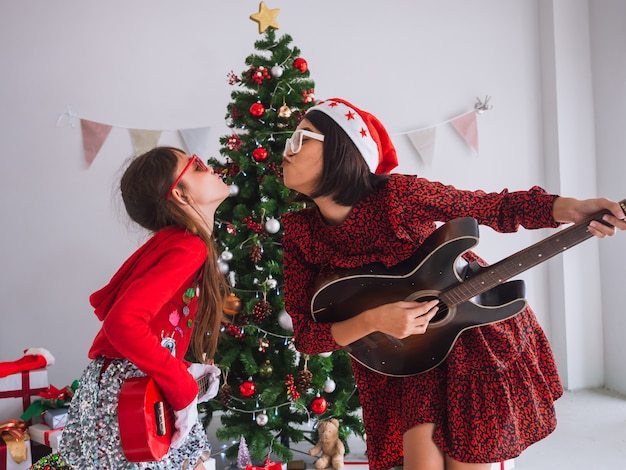 Asian women and kid celebrate christmas by struming the guitar in house