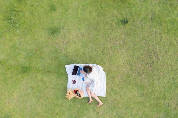 アジアの女性は緑の芝生でリラックスして働くラップトップについてうそをつきます
