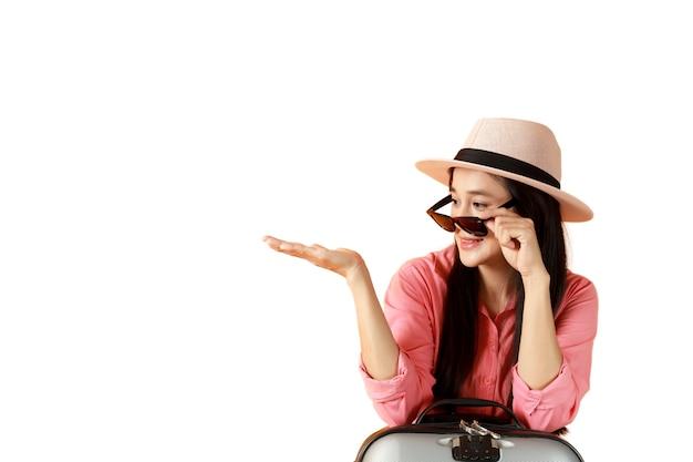 アジアの女性の長い髪は旅行バッグを開いて帽子とサングラスを着用します
