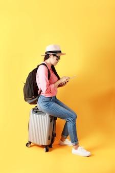 アジアの女性の長い髪は、手に持ってタブレットを使用して旅行バッグに座って麦わら帽子とサングラスを着用します