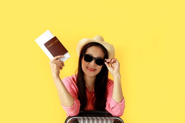 アジアの女性の長い髪は麦わら帽子、パスポートの本と旅行バッグを持っている手にサングラスを着用します