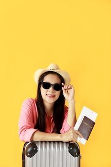 アジアの女性の長い髪は麦わら帽子、パスポートの本を持っている手にサングラスを着用します