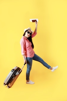 Asian women long hair wear straw hat with black ribbon in hand holding passport book and travel bag.