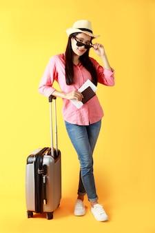 アジアの女性の長い髪は、パスポートの本と旅行バッグを持っている手に黒いリボンの麦わら帽子をかぶっています。