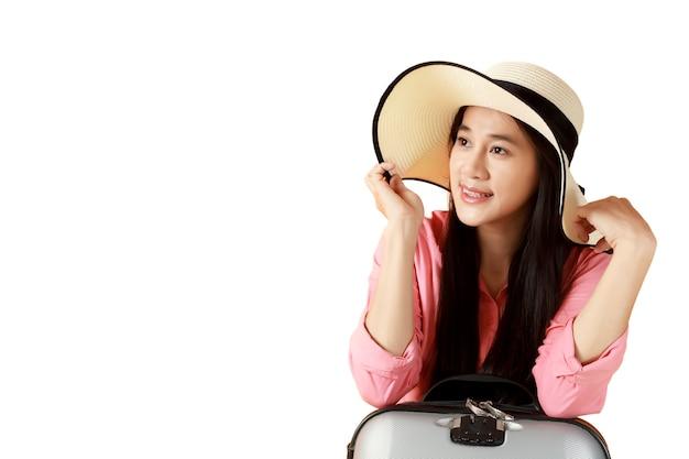 アジアの女性の長い髪は旅行バッグと麦わら帽子を着用します