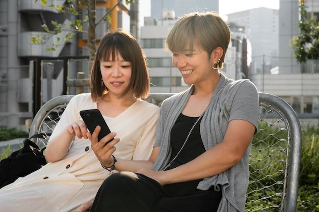 電話で何かを見ているアジアの女性