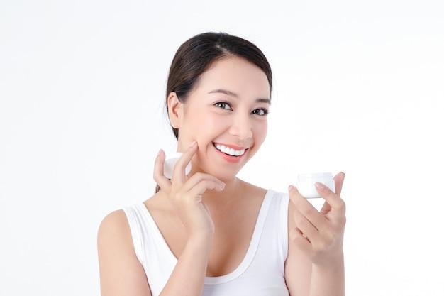 아시아 여성은 건강을 좋아하고 피부가 깨끗하고 아름답고 바디 크림을 바르십시오. 뷰티 컨셉