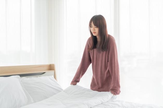 Азиатские женщины заправляют кровать в комнате с белой чистой простыней