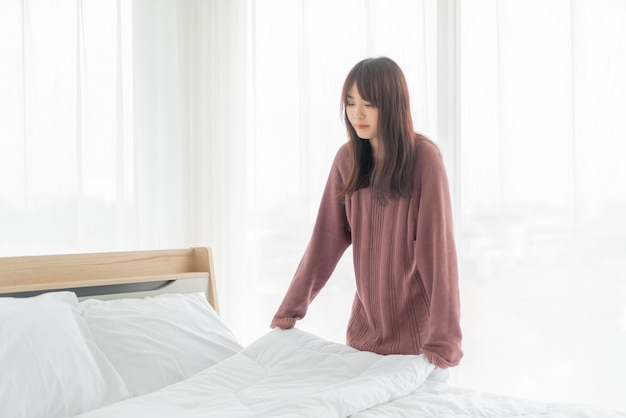 Asian women making bed in room with white clean sheet