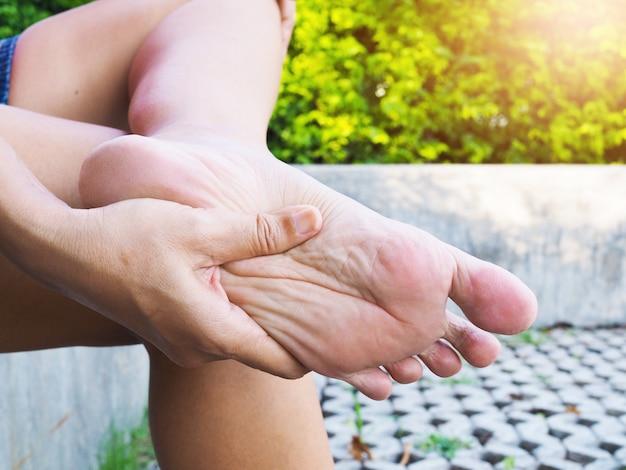 Азиатские женщины массажируют на каблуках, страдающих от боли в пятке, травмы стопы с хронической болью