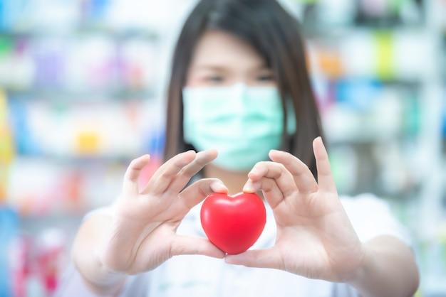 Врач азиатских женщин держа красный шарик сердца с запачканной концепцией здравоохранения.