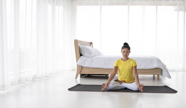 Asian women meditate while practicing yoga