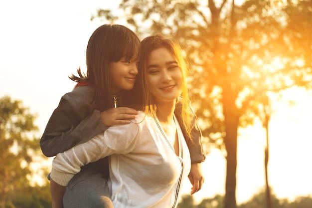 Азиатские женщины мать и девушка целуя и обнимая в парке на заходе солнца.