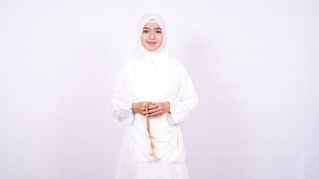 アジアの女性イスラム教徒は白い壁に祈る