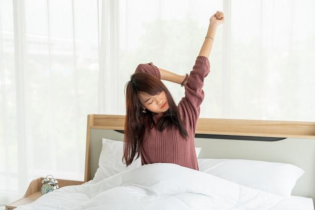 ベッドで朝目を覚ますアジアの女性